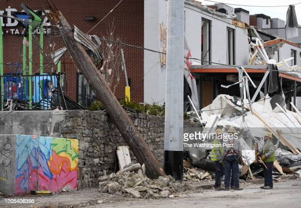 Workers stand near damage in the Five Points area on Thursday March 05 2020 in Nashville TN Tornados hit the area early Tuesday morning