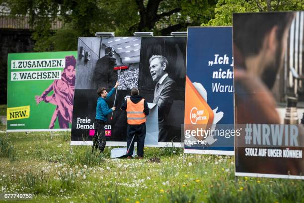Workers stand near election campaign billboards of Free Democratic Party Freie Demokratische Partei or FDP the German Social Democrats the German...