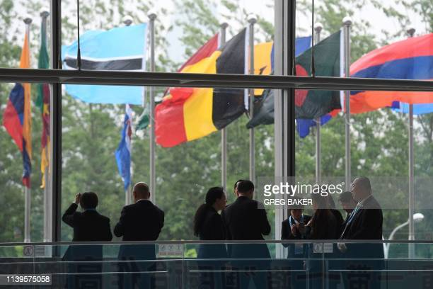 Workers stand near flags of countries participating in the Belt and Road Forum at one of the venues of the forum in Beijing on April 27 2019 Chinese...