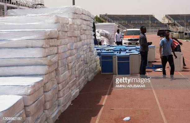 Workers stand near stacks of hospital mattresses brought for a COVID-19 coronavirus isolation centre at the Sani Abacha stadium in Kano, Nigeria, on...