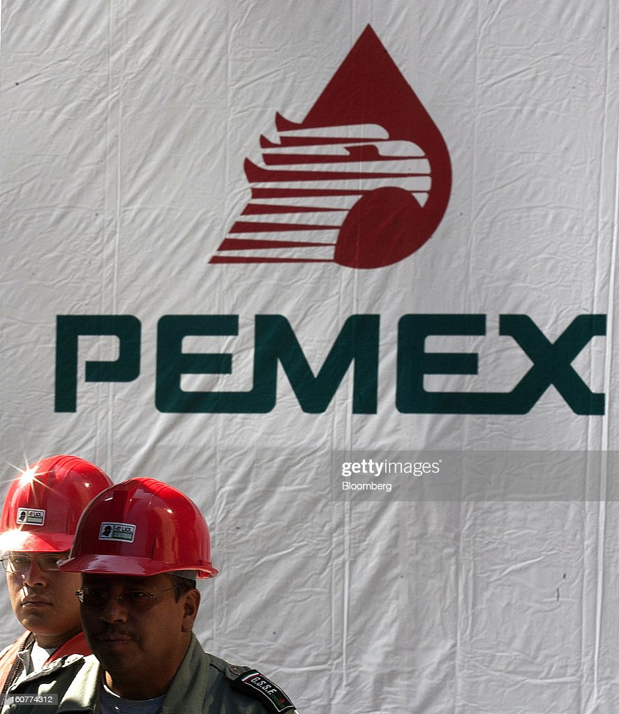 Workers stand next to a banner with the Petroleos Mexicanos (Pemex) logo on it at the blast site at company headquarters in Mexico City, Mexico, on Tuesday, Feb. 5, 2013. Mexican authorities said a buildup of gas led to the blast last week that killed 37 people at Petroleos Mexicanos's headquarters, the first official attempt to explain the nation's deadliest explosion since 2006. Photographer: Susana Gonzalez/Bloomberg via Getty Images