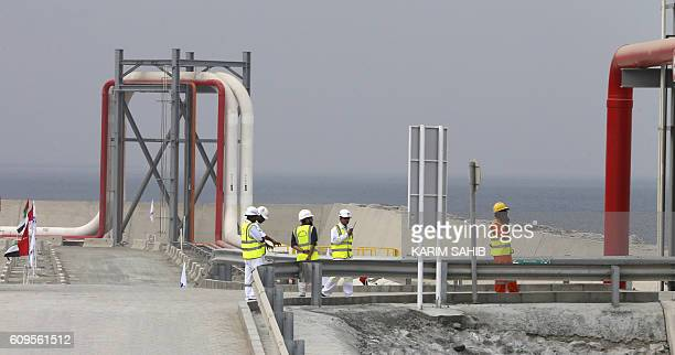 Workers stand next to a pipeline at the oil terminal of Fujairah during the inauguration ceremony of a dock for supertankers on September 21 2016 The...