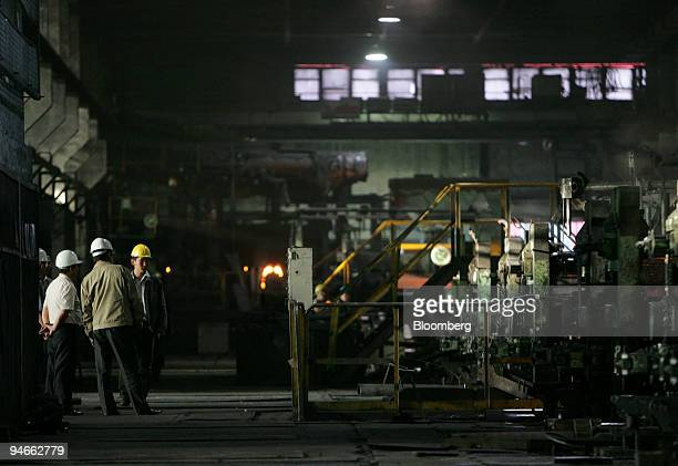 Workers stand next to machinery in the Darkhan Metallurgical plant 220km north of Ulaanbaatar, Mongolia, on Friday, September 15, 2006.