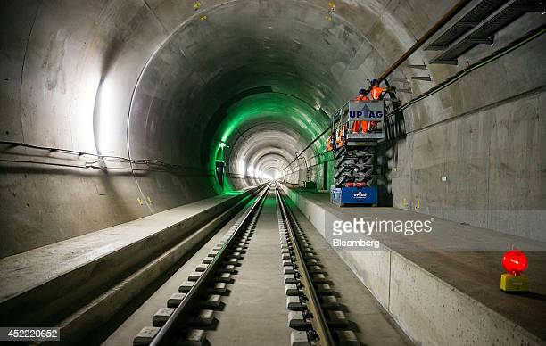Workers stand on a scissor lift as they fix cable support trays to the access tunnel wall inside the west section of the Gotthard Base Tunnel in...