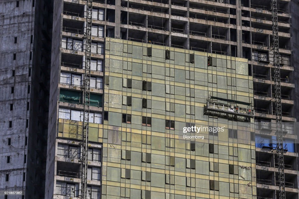 Workers stand on a suspended platform at one of the two towers of Trump Tower Mumbai under construction at Lodha The Park, a luxury residential project developed by Lodha Developers Ltd., in Mumbai, India, on Tuesday, Feb. 20, 2018. India has the most construction projects with Trump licensing deals of any country outside of the U.S. Photographer: Dhiraj Singh/Bloomberg via Getty Images