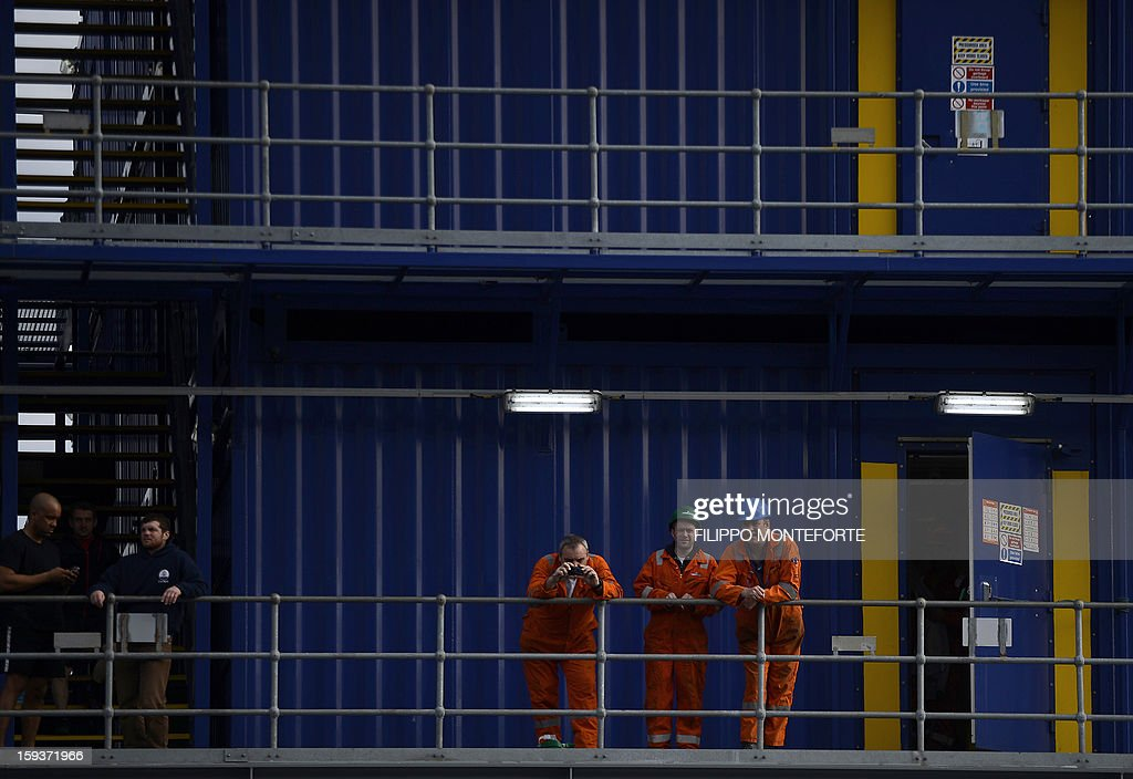 Workers stand on an accomodation boat in front of the Costa Concordia cruise ship in the port the Italian island of Isola del Giglio on January 12, 2013. A year on from the Costa Concordia tragedy in which 32 people lost their lives, the giant cruise ship still lies keeled over on an Italian island and its captain Francesco Schettino has become a global figure of mockery.