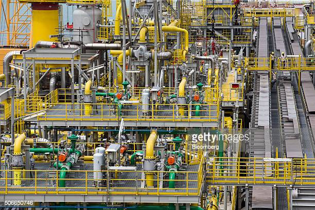 Workers stand on an elevated walkway on the Tullow Oil Plc Prof John Evans Atta Mills Floating Production Storage and Offloading vessel docked at the...