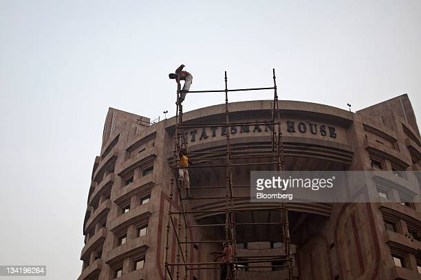 Workers stand on scaffolding outside the Statesman House building in Connaught Place in New Delhi India on Saturday Nov 26 2011 Morgan Stanley...