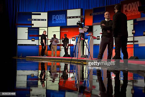Workers stand on stage ahead of the Republican presidential candidate debate at the North Charleston Coliseum and Performing Arts Center in North...