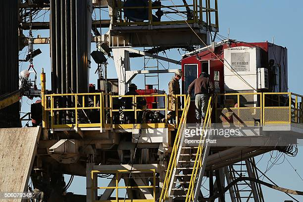 Workers stand on the platform of a fracking rig in the Permian Basin oil field on January 21 2016 in the oil town of Midland Texas Despite recent...