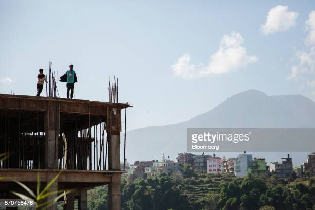Workers stand on the roof of a commercial building under construction in Kathmandu Nepal on Wednesday Nov 1 2017 India and China have often jostled...