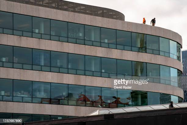 Workers stand on the roof of the Bill and Melinda Gates Foundation on May 4, 2021 in Seattle, Washington. Bill Gates and Melinda Gates announced...