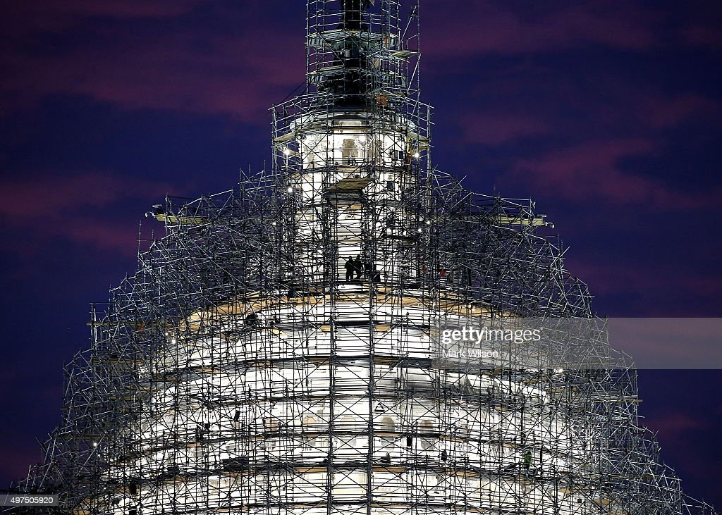 Workers stand on the scaffolding that surrounds the dome of the US Capitol which is undergoing restoration, November 17, 2015 in Washington, DC. The restoration of the cast iron dome is expected to take two years and cost as much as 60 million dollars