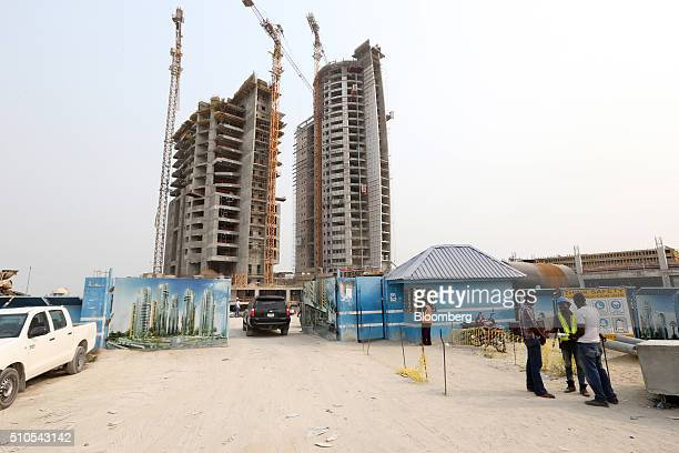 Workers stand outside the site entrance for the Eko Pearl Towers residential development at the Eko Atlantic city site, developed by Eko Atlantic,...