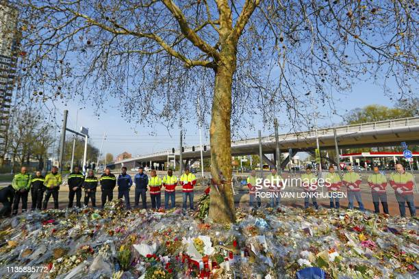 TOPSHOT Workers stand to pay tribute before taking away flowers and items left in remembrance of the victims near the scene of the attack on a tram...