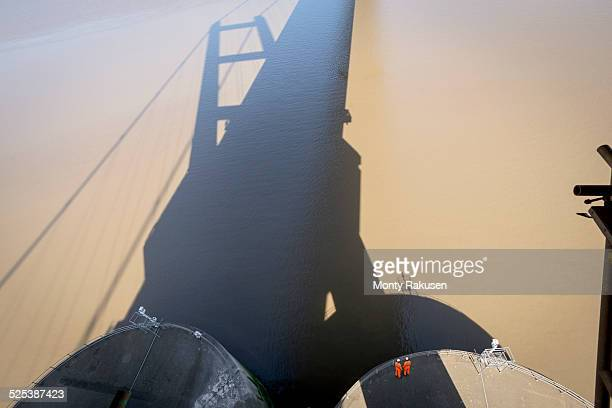 Workers standing in the shadow of suspension bridge. The Humber Bridge, UK was built in 1981 and at the time was the worlds largest single-span suspension bridge