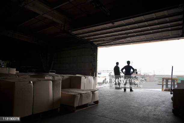 workers standing on loading dock of factory - loading dock stock pictures, royalty-free photos & images