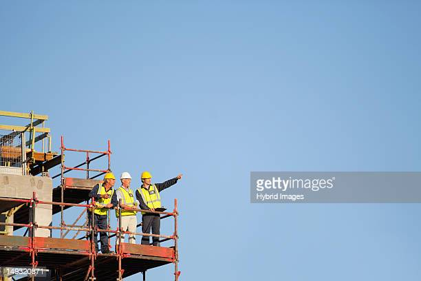 Workers standing on scaffolding on site