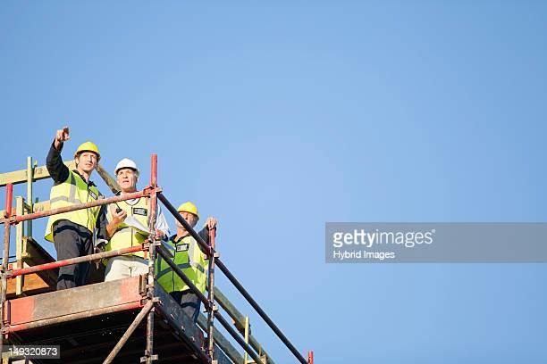 workers standing on scaffolding on site - veiligheidshek stockfoto's en -beelden