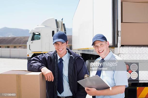 Travailleurs debout avec boîtes à proximité de semi-remorque