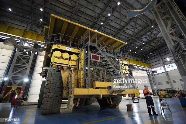 A workers stands near a Komatsu Ltd dump truck inside the truck shop at the Oyu Tolgoi coppergold mine jointly owned by Rio Tinto Group's unit...