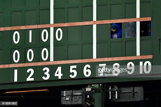 Workers stick their heads out of the scoreboard during the 2016 World Series Game 5 between the Cleveland Indians and the Chicago Cubs on October 30...
