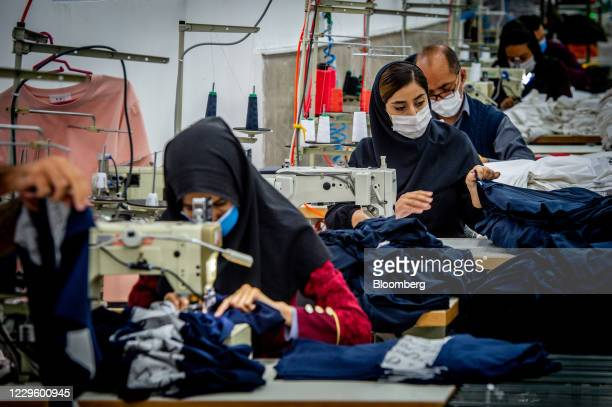 Workers stitch Iranian brand jeans, including Koi designed garments, at a clothing factory on the outskirts of Tehran, Iran, on Wednesday, Oct. 14,...