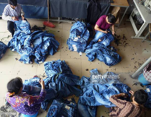 Workers stitch jeans at a small factory in Zengcheng on June 15, 2011. Residents of a southern Chinese town described frightening scenes of...