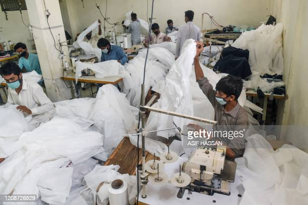 Workers stitch medical clothing and protective gear during a governmentimposed nationwide lockdown against the COVID19 coronavirus at a factory in...