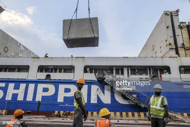 Workers supervise a block of limestone being loaded on to the Da Dan Xia cargo ship at Krishnapatnam Port in Krishnapatnam Andhra Pradesh India on...