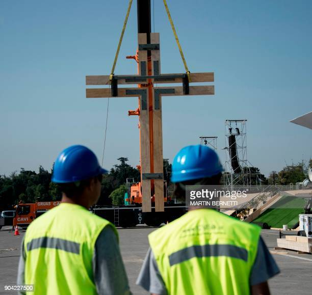 Workers supervise as a huge wooden cross is placed with a crane near the stage in which Pope Francis will officiate the first open airmass during his...