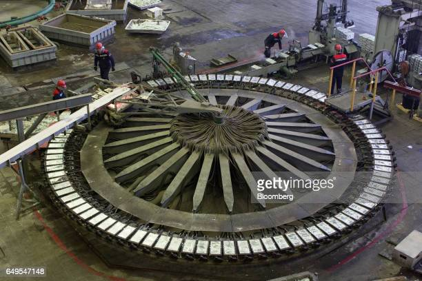 Workers supervise the pouring of zinc ingots in the rotary foundry room at the Chelyabinsk Zinc Plant operated by Ural Mining and Metallurgical Co in...