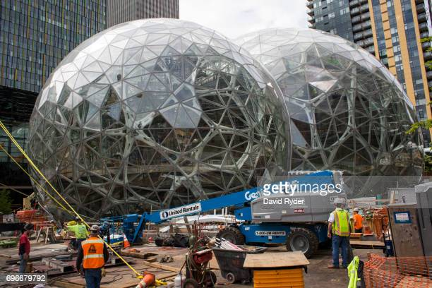Workers surround the signature glass spheres under construction at the Amazon corporate headquarters on June 16 2017 in Seattle Washington Amazon...