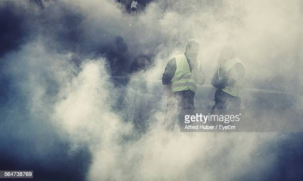 workers surrounded by smoke - 囲む ストックフォトと画像