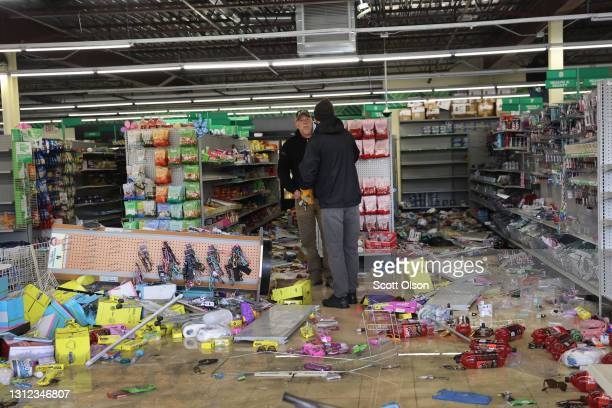 Workers survey damage to a Dollar Tree store in a strip mall near the Brooklyn Center police station after it was vandalized and looted during the...