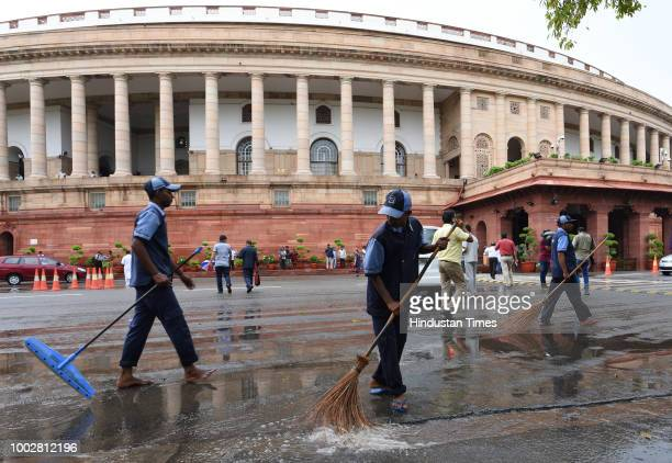 Workers sweep a waterlogged area due to heavy rainfall in the national capital in front of Parliament House building during the third day of the...