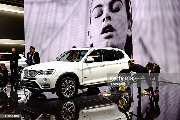 Workers sweep the floor as a BMW X3 sportutility vehicle manufactured by Bayerische Motoren Werke AG sits on display during the second press day of...