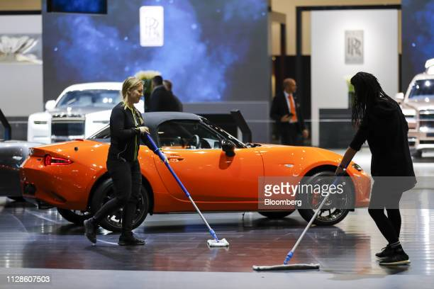 Workers sweep the floor in front of a Mazda MX5 automobile manufactured by Mazda Motor Corp stand ahead of the 89th Geneva International Motor Show...