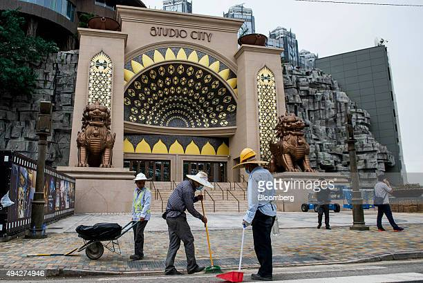 Workers sweep the road in front of an entrance to Studio City casino resort developed by Melco Crown Entertainment Ltd in Macau China on Monday Oct...