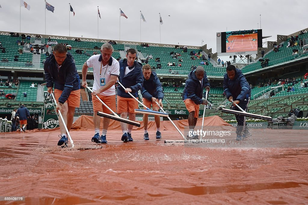 TOPSHOT - Workers sweep the water off from the tarp covering the central court at the Roland Garros 2016 French Tennis Open in Paris on May 22, 2016. / AFP / Eric FEFERBERG