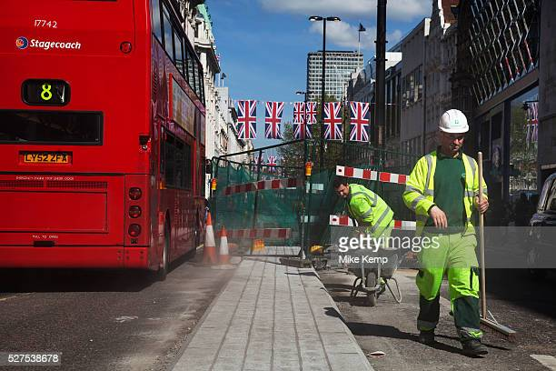 Workers sweep up as improvements take place underneath Union Jack flags in central London on Oxford Street UK This is the most famous street in the...