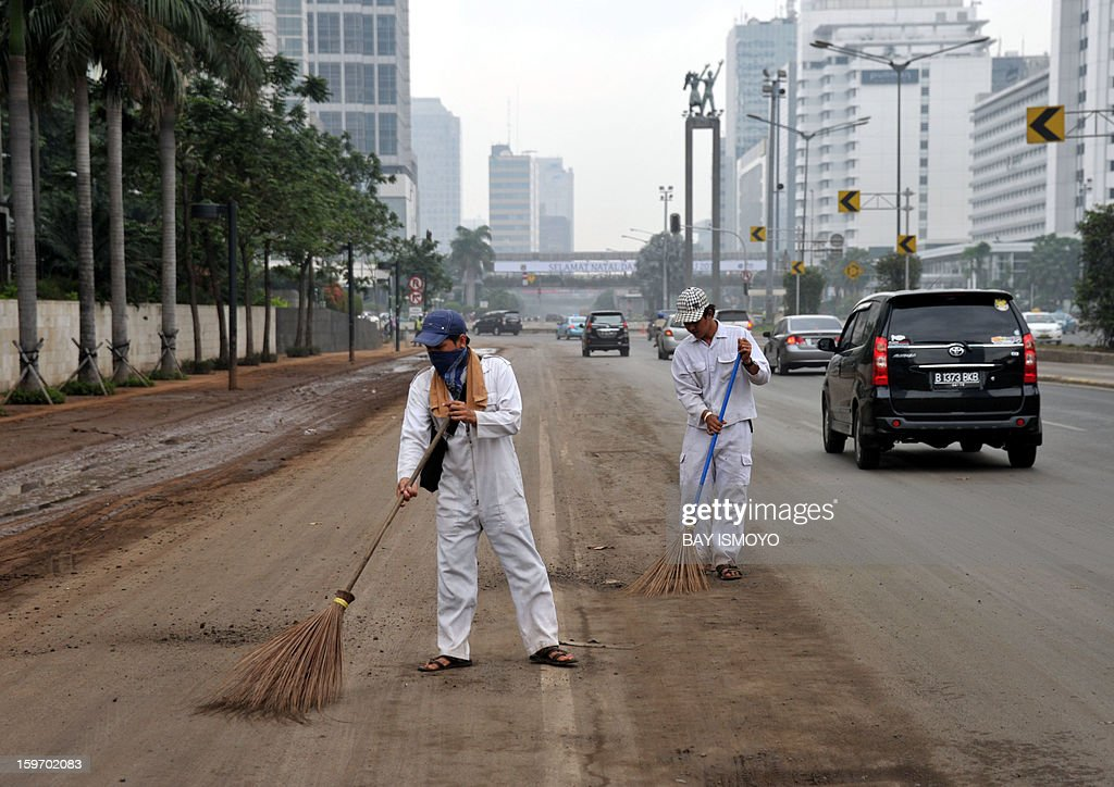 Workers sweep up Jakarta's downtown main road on January 19, 2013 which was hit by massive flood on January 17. Floods in Indonesia's capital Jakarta killed 15 people as rescuers found another four bodies, a police spokesman said. AFP PHOTO / Bay ISMOYO