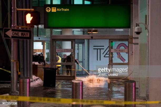Workers sweep water from a floor of the arrivals area at John F Kennedy International Airport's terminal 4 in New York on January 7 2018...