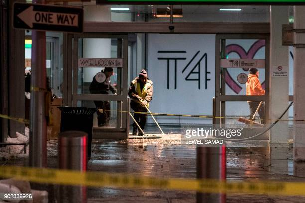 Workers sweep water from floor of the arrivals area at John F Kennedy International airport's terminal 4 in New York on January 7 2018 International...