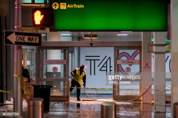Workers sweep water from the floor of the arrivals area at John F Kennedy International airport's terminal 4 in New York on January 7 2018...