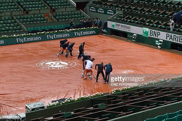 Workers sweep water off a tarp covering the central court before the first round match at the Roland Garros 2016 French Tennis Open in Paris on May...