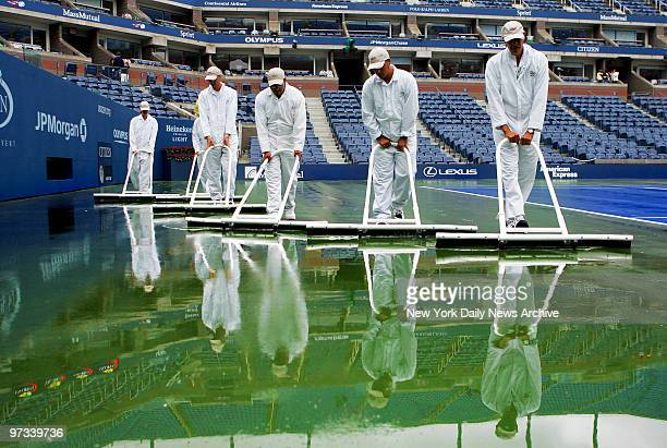 Workers sweep water off the court at Arthur Ashe Stadium during a rain delay at the US Open in Flushing MeadowsCorona Park Due to the heavy downpour...