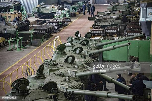 Workers take a break beside the renovated gun turrets of T72 battle tanks during the repair of heavy armor in the military workshop operated by...
