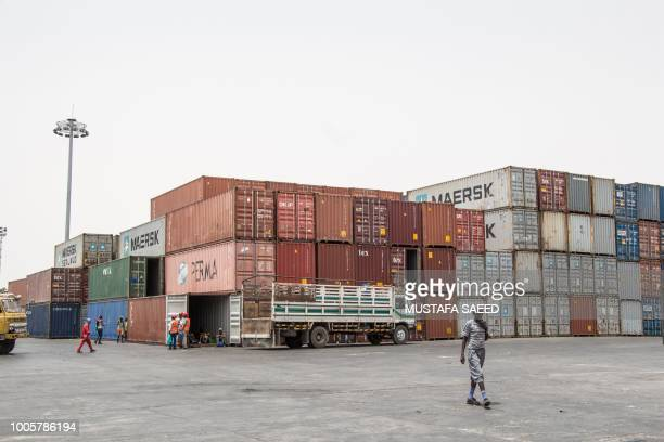 Workers take a break in a container during the unloding of NOGs' food ratios from a ship at Berbera port of Somaliland on July 21, 2018. - The...