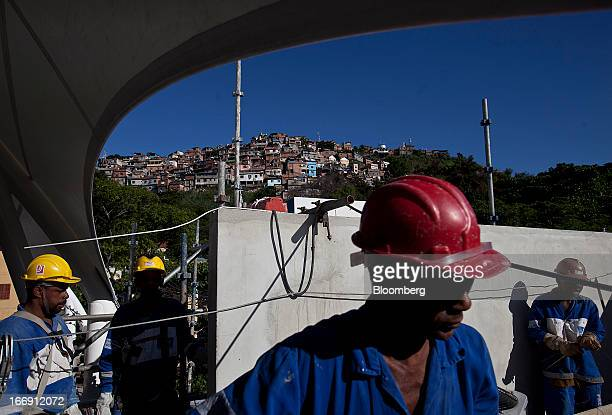 Workers take a break while finishing construction details on the rooftop of the Gamboa cable car station in Rio de Janeiro, Brazil, on Tuesday, April...